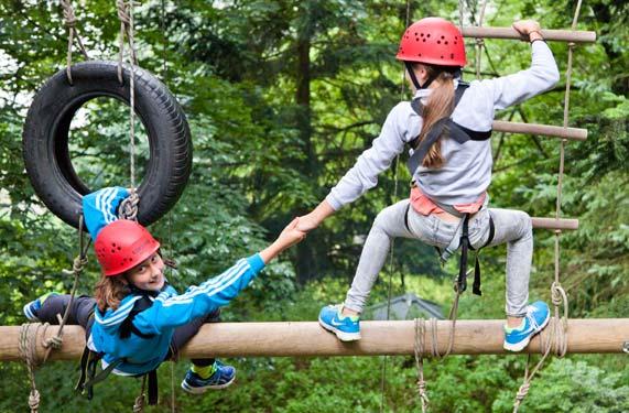 Maedchen auf Riesenleiter im AbenteuerCamp Zorge