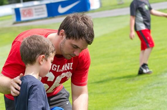 Betreuer kümmert sich um Teilnehmer im Oskar-Fussball DayCamp Olympiapark
