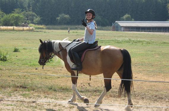 In den Reitferien hält Reiterin die Hand zum Viktoryzeichen.