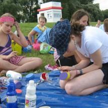 Teilnehmer des Sport- u. KreativCamps Welper beim Basteln auf der Wiese