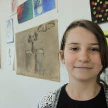 Eine junge Künstlerin vor der Bildergalerie im Kunst- und KreativCamp Wegscheide
