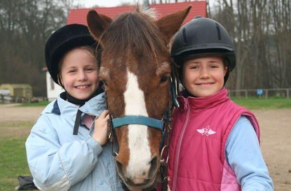 Zwei Mädchen stehen links und rechts vom Pferd und freuen sich.